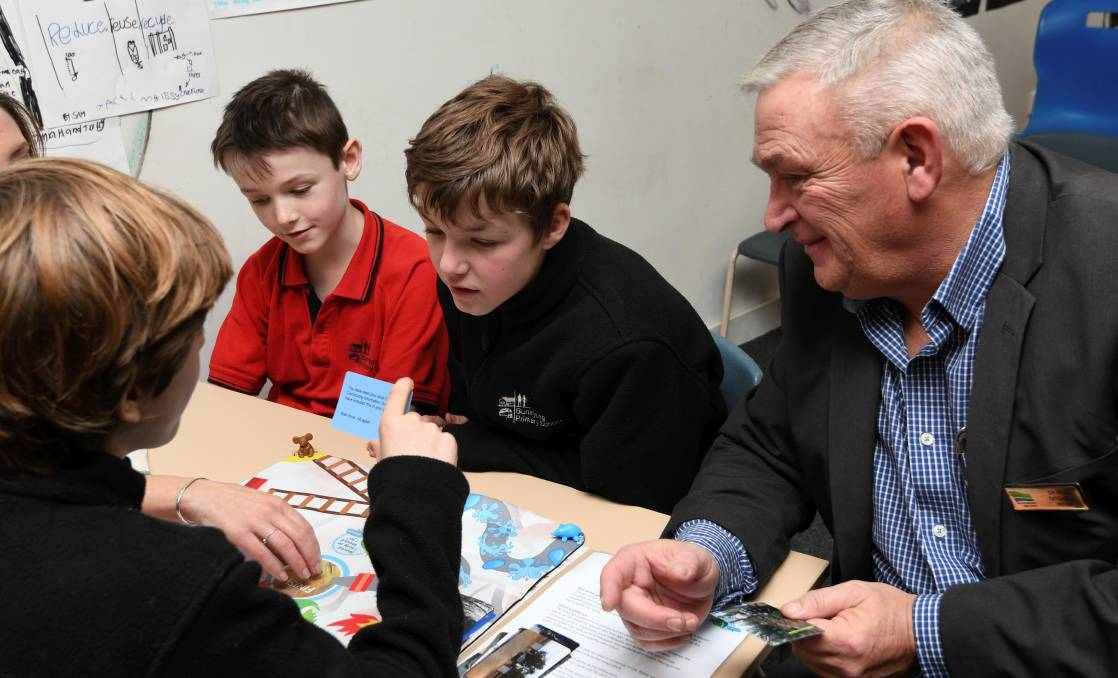 GAME TIME: Scotsburn pupils Pat, Charlie and Will play Should I Stay or Should I Go? with Moorabool mayor Cr Paul Tatchell. Picture: Lachlan Bence